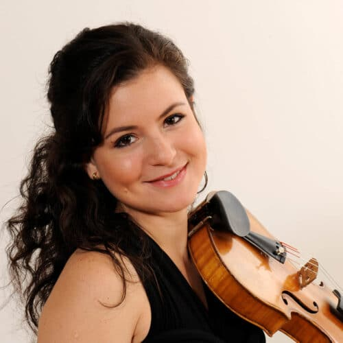 Violin and viola teacher at klaudias music studio in oakville holding violin